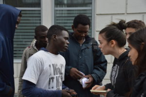 Student Tailor Liedtke (right) interviews Sudanese refugees on the Avenue de Flandre in Paris. Photo by Sloane Valen/ASP.