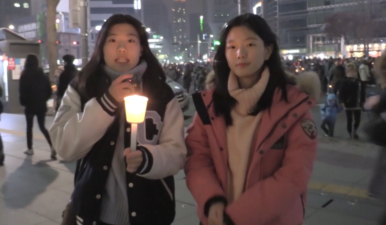 Students NAME And Haeji Kim At The Scene Of A Protest In Seoul On Nov. 27. Demonstrators Called For President Park To Step Down From Office Amid A Widening Political Corruption Scandal. Screenshot By GSS Staff.